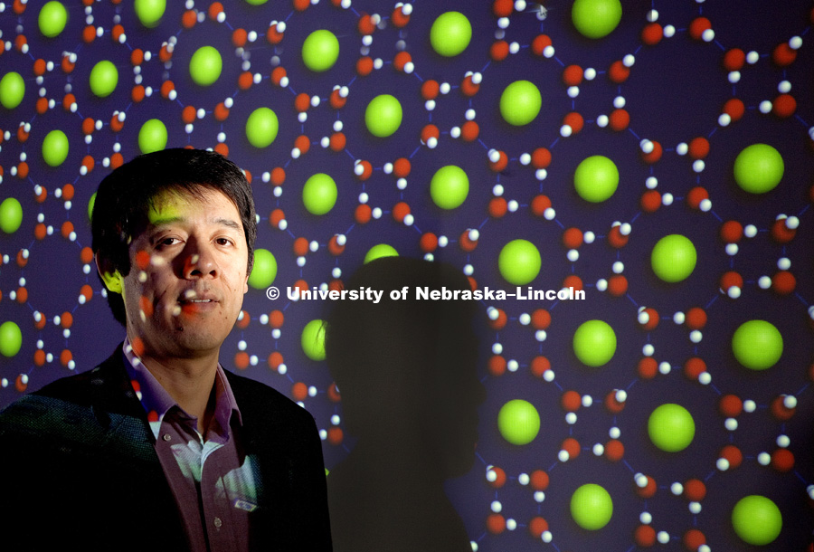 Xiao Cheng Zeng, Ameritas University Professor and Willa Cather Emeritus Professor.  He is shown with computer generated renderings of his work behind him. Square-octagon ice clathrate with argon atoms (green) inside octagonal openings is the multi green sphere image. Single-walled Hexagonal Silicon Nanotube. 100331, Photo by Craig Chandler / University Communications