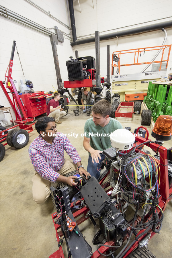 Santosh Pitla discusses the electronics on a robotic cart with Tyler Troyer, graduate student in BSE. Robotics lab on east campus. Biological Systems Engineering. August 15, 2016. Photo by Craig Chandler / University Communication.