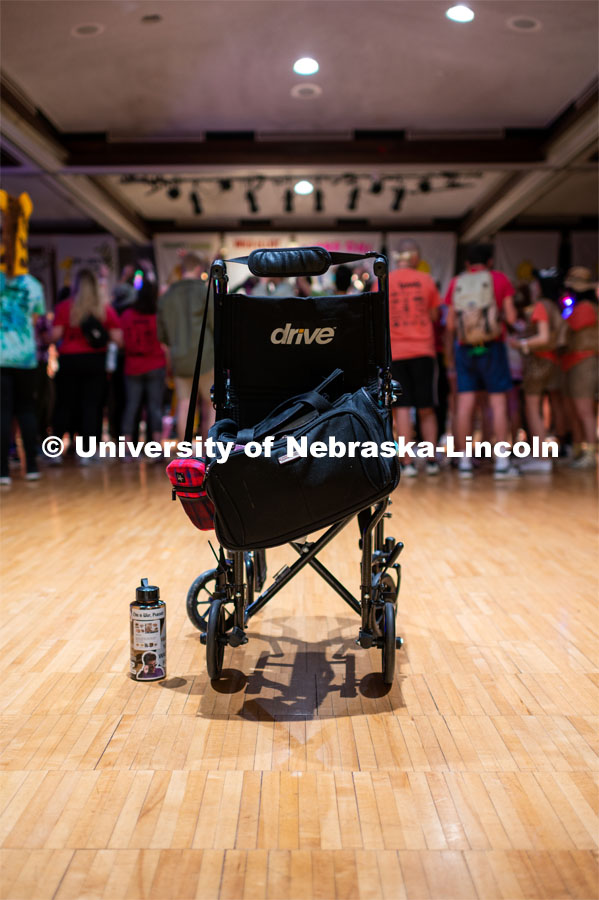 "A wheelchair of one of the miracle children sits empty as they are in the group enjoying themselves. University of Nebraska–Lincoln students exceeded their goal, raising $235,229 during the annual HuskerThon on Feb. 29. Also known as Dance Marathon, the event is part of a nationwide fundraiser supporting Children's Miracle Network Hospitals. The annual event, which launched in 2006, is the largest student philanthropic event on campus. The mission of the event encourages participants to, ""dance for those who can't."" All funds collected by the Huskers benefit the Children's Hospital and Medical Center in Omaha. February 29, 2020. Photo by Justin Mohling / University Communication."