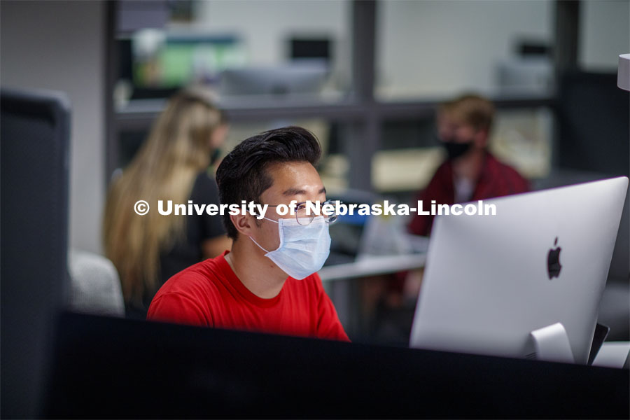A masked student works on a computer in Anderson Hall. Photo shoot of students wearing masks and practicing social distancing. August 11, 2020 Photo by Craig Chandler / University Communication.