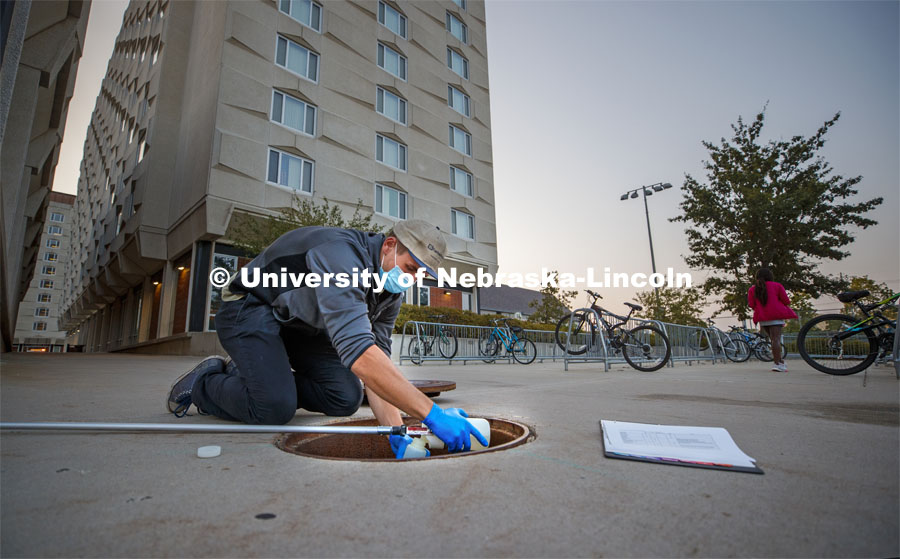 Spencer Perry, graduate student in environmental engineering, takes a wastewater sample from the sewer flowing from Smith Residence Hall. He and Shannon Bartelt-Hunt, professor in civil engineering, are sampling wastewater from UNL residence halls for COVID research. September 24, 2020 Photo by Craig Chandler / University Communication.