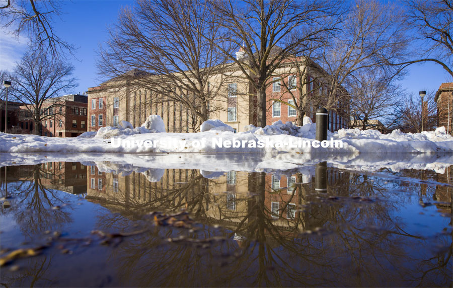 Love Library is reflected in a puddle along the drive behind Canfield Hall. February 22, 2021. Photo by Craig Chandler / University Communication.
