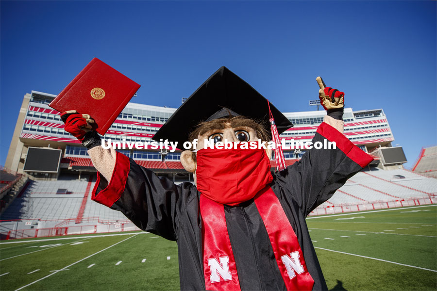 A masked Herbie Husker holding a diploma, poses in regalia to announce spring commencement will be in Memorial Stadium. March 1, 2021. Photo by Craig Chandler / University Communication.