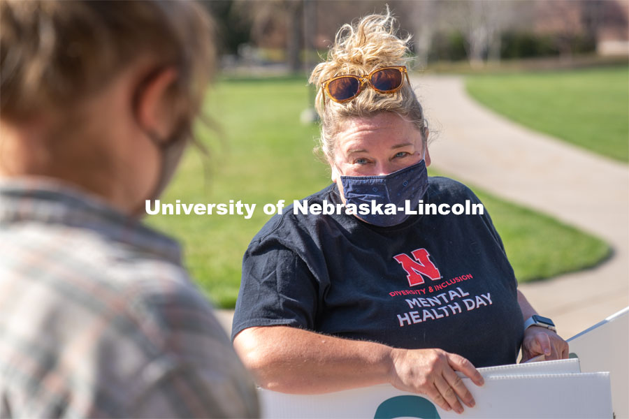 CARE Advocate Melissa Wilkerson speaks to volunteers before setting up their display at the Nebraska Union Greenspace. Flags and signs are placed in the Nebraska Union Greenspace to promote Sexual Assault Awareness Month. April 4, 2021. Photo by Jordan Opp for University Communication.