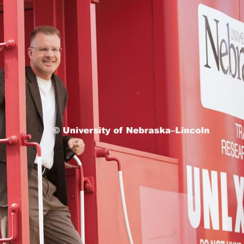 Dr. Shane Farritor poses on a caboose custom painted and donated to the University of Nebraska–Lincoln. The Husker red caboose was used to house the measuring equipment and generators used on the first-generation test car. The current test car is a self-contained hopper car. Track modulus is one of several indicators for the quality and performance of railroad track. It is the ratio of vertical rail deflection and the contact pressure between the rail base and track foundation.Photo by Craig Chandler / University Communications