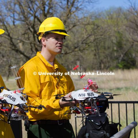 Professor Carrick Detweiler describes to the media how the drone will drop a small ball to start the burn.  The ball has a chemical powder in it and while airborne, the drone will inject a second chemical.  The drone then drops the ball and it bursts into