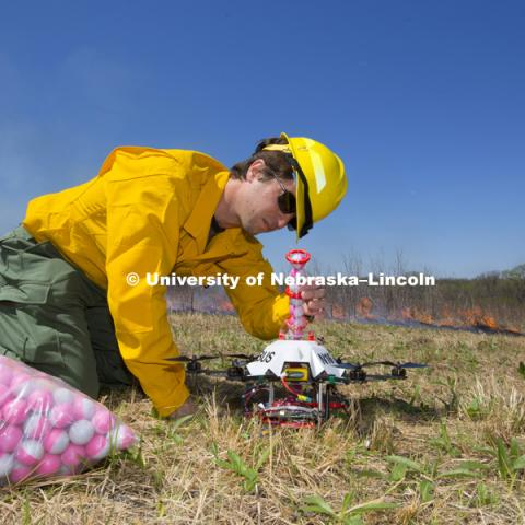 Sebastian Elbaum checks over the tube of balls before the drone takes off. Controlled burn at the Homestead National Monument in Beatrice, NE. Sebastian Elbaum and Carrick Detweiler have engineered a drone able to light controlled prairie burns using