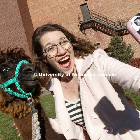 Alison Finn, a senior in secondary English education and theater, takes a selfie with Mahogany, an alpaca, outside the Visitors Center Wednesday.  It was brought to campus as part of a theater department costume class where students had to design costumes