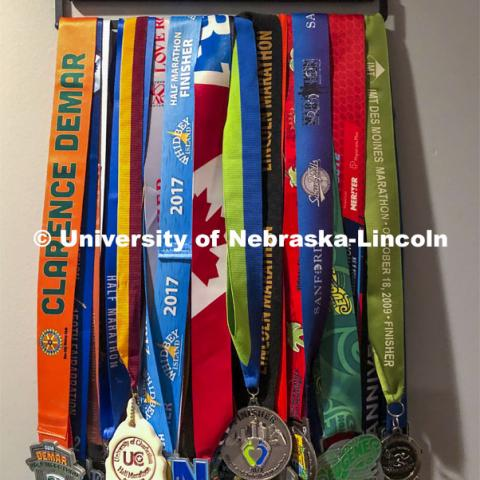 Pictured: Sue Sheridan's running medals. Sue Sheridan, director of the Nebraska Center for Research on Children, Youth, Families and Schools, is on a mission to run marathons or half-marathons in all 50 states. Sheridan is running in support of her nonprofit, Elevating Haitian Education. Sue is pictured running at Holmes Lake Park in Lincoln, Nebraska. December 4, 2019. Photo by Craig Chandler / University Communication.