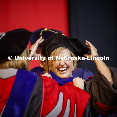 Heather Vorrhees laughs as her cap is knocked askew while being hooded at the Graduate Commencement and Hooding at the Pinnacle Bank Arena. December 20, 2019. Photo by Craig Chandler / University Communication.