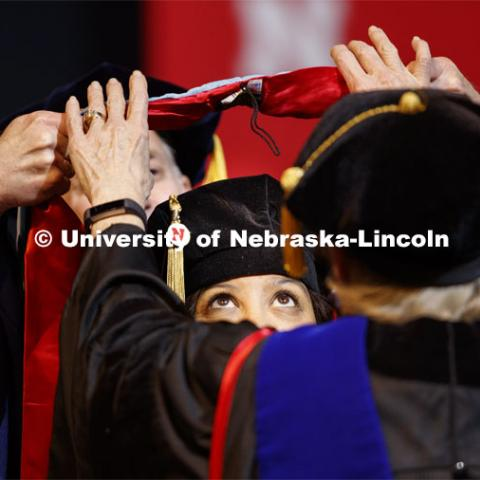 Brandi Bibins-Redburn has her eyes on the prize as her Doctor of Education hood is lowered over her head. Graduate Commencement and Hooding at the Pinnacle Bank Arena. December 20, 2019. Photo by Craig Chandler / University Communication.