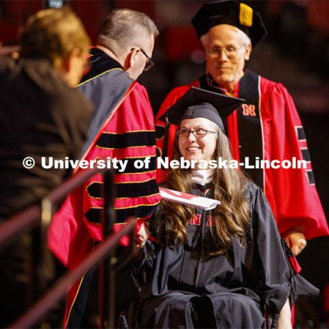 A young woman receives her diploma from Chancellor Ronnie Green. Graduate Commencement and Hooding at the Pinnacle Bank Arena. December 20, 2019. Photo by Craig Chandler / University Communication.
