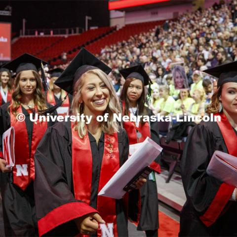 Alyssa Arndt smiles as she walks past her family cheering section. The family all wore neon green shirts so Alyssa wouldn't miss seeing them. December Undergraduate commencement at Pinnacle Bank Arena. December 21, 2019. Photo by Craig Chandler / University Communication.