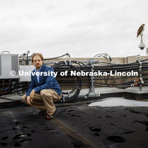 Gus Hurwitz, Nebraska Law professor researching rural broadband issues in Nebraska. He is amongst the telecommunications equipment that covers the roof of Oldfather Hall. January 31, 2020. Photo by Craig Chandler / University Communication.
