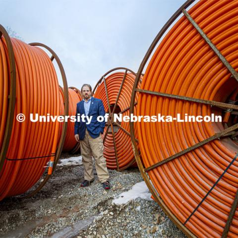 Gus Hurwitz, Nebraska Law professor researching rural broadband issues in Nebraska. Behind him are coils of conduit used to bury fiber cable. January 31, 2020. Photo by Craig Chandler / University Communication
