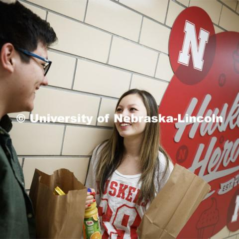 Selleck Dining Center photo shoot. Students standing next to the Husker Heroes logo in Selleck Dining Center. March 5, 2020. Photo by Craig Chandler / University Communication.