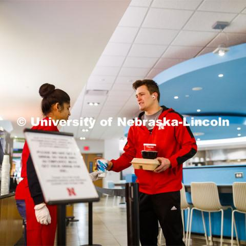 Zachery Borer, a freshman from North Bend, NE, collects his drink and lunch to-go from Manpreet Kaur in the Willa S. Cather Dining Complex on City Campus. March 17, 2020. Photo by Craig Chandler / University Communication.