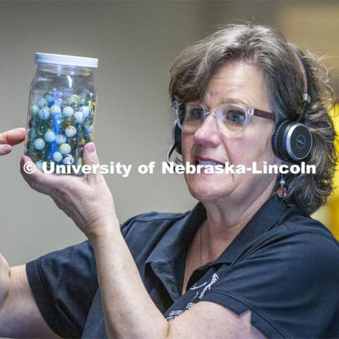 Annie Mumgaard, Virtual Learning Coordinator for the University Museum, uses a jar full of marbles to describe how individual rocks, like the marbles, can then be transformed by heat and pressure into metamorphic rock. April 14, 2020. Photo by Craig Chandler / University Communication.