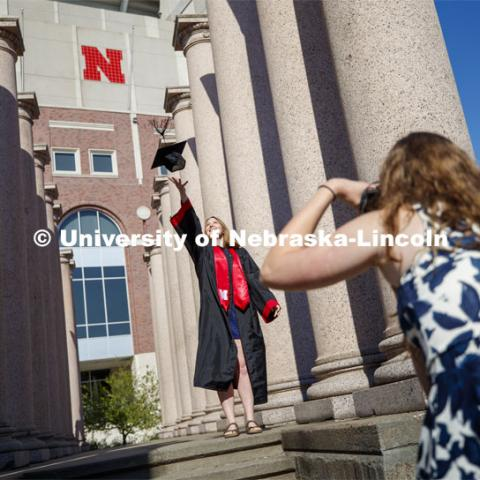Rose Wehrman, senior in English, from Kenesaw, NE, is photographed by Sarah Schilling, senior in marketing from Omaha. The two borrowed a cap and gown (from a friend who graduated last year) to take photos of each other on campus Thursday morning. April 30, 2020. Photo by Craig Chandler / University Communication.