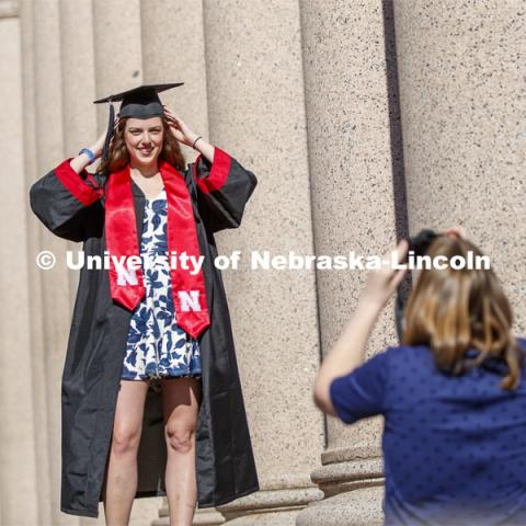 Sarah Schilling, senior in marketing from Omaha, is photographed by Rose Wehrman, senior in English, from Kenesaw, NE. The two borrowed a cap and gown (from a friend who graduated last year) to take photos of each other on campus Thursday morning. April 30, 2020. Photo by Craig Chandler / University Communication.