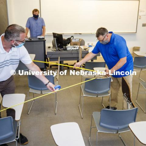 Jack Dohrman, Interim University Space Manager, with Facilities Management and Planning, and Shawn Languis, Space Planning/GIS Data Coordinator with Facilities Management and Planning use tape measures to gauge physical distancing needs within an Avery Hall classroom. Based on their measurements, seating in this classroom will shift from 35 desks in a regular semester to 14 in the fall. The change allows the university meet the six-foot social distancing needs related to COVID-19. In large lecture halls, seating capacity is expected to be reduced to 20 percent. Keith Derickson, Academic Technologies Support Manager, stands in the instructor position. A group is physically measuring every classroom on campus to see if computer-aided predictions are correct. June 1, 2020. Photo by Craig Chandler / University Communication.
