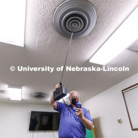 Dave Tyler, Control Systems Tech, uses a hot wire anemometer to measure air coming from a vent in a practice room in Westbrook Music Building. To mitigate the risk of virus transfer within the buildings, the facilities team is increasing by nearly 50 percent the amount of fresh air being drawn into HVAC systems. They are also upgrading filters to more efficiently capture and reduce large and small particles in the air. July 27, 2020. Photo by Craig Chandler / University Communication.
