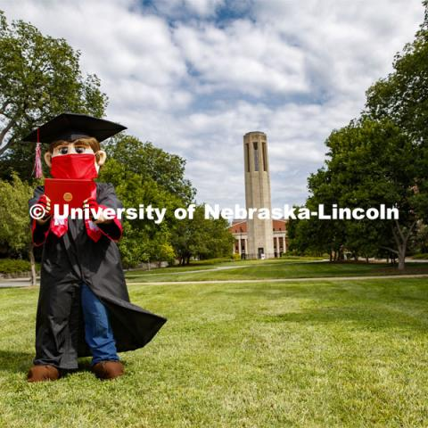 Herbie Husker has a protective mask on while he poses in front of the Mueller Bell tower while wearing a graduation cap and gown. On campus. August 5, 2020. Photo by Craig Chandler / University Communication.