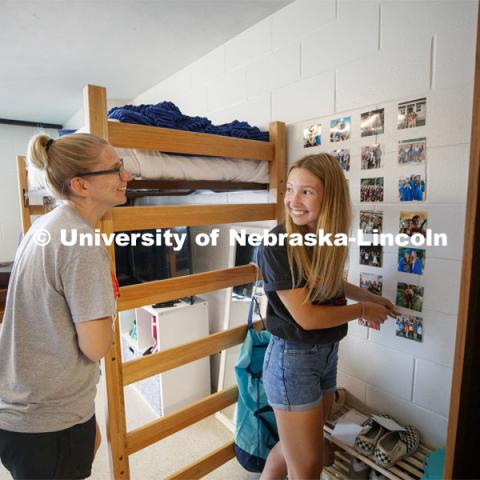 Miqaela Davis, right, from Omaha, smiles at her mom, Monica, after finishing decorating one of her walls. First day of residence hall move in. August 13, 2020. Photo by Craig Chandler / University Communication.