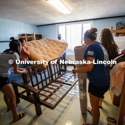 Shanelle Flores' family puts her futon together in her Harper Hall room. First day of residence hall move in. August 13, 2020. Photo by Craig Chandler / University Communication.
