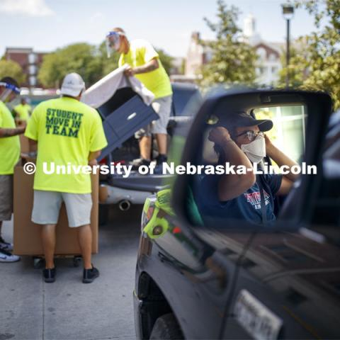 The Student Move-In Team unloads a truck. A student masks up while waiting for his turn to unload at Knoll Residence Hall. First day of residence hall move in. August 13, 2020. Photo by Craig Chandler / University Communication.