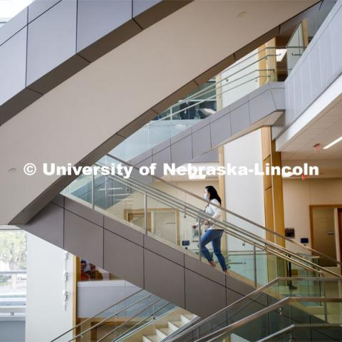 A young woman walking up the stairs in Hawks Hall. September 14, 2020. Photo by Craig Chandler / University Communication.