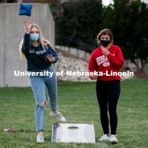 Representatives of Alpha Omicron Pi and Chi Omega alternate tossing beanbags during the ASUN Cornhole Competition at the Cather-Pound Greenspace on Wednesday, October 28, 2020, in Lincoln, Nebraska. Photo by Jordan Opp for University Communication.