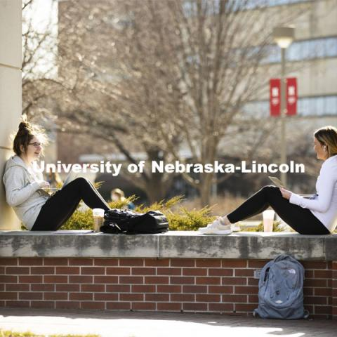 Madison Moran, left, a freshman from Kansas City, and Jenna Craven, a freshman from Norfolk, enjoy the warm sunshine. Warm weather on city campus. March 4, 2021. Photo by Craig Chandler / University Communication
