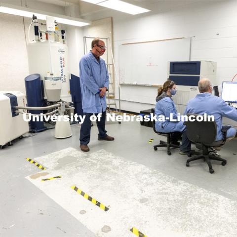 Pat Dussault, Michelle Takacs and Dan Draney look over results from the Research Instrumentation Facility's high-field NMR (nuclear magnetic resonance) spectrometer in Hamilton Hall. April 6, 2021. Photo by Craig Chandler / University Communication.