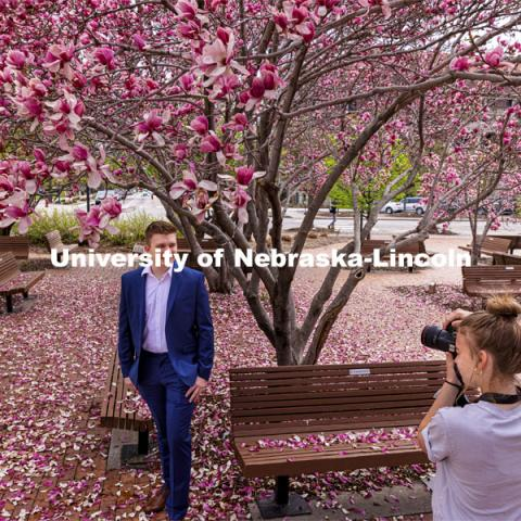 Lucas Zelnio has his photo taken by Avery Bowman under the Saucer Magnolia trees blooming outside of the Lied Center. Spring on City Campus. April 6, 2021. Photo by Craig Chandler / University Communication.
