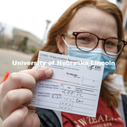 Heather Hunt, senior in Animal Science with the Meat Science option and minoring in Agriculture and Environmental Sciences Communications, shows off her vaccine card after receiving her second shot. More than 150 UNL faculty, staff and student volunteers are helping at the COVID vaccine clinic at Pinnacle Bank Arena this week. April 7, 2021. Photo by Craig Chandler / University Communication.