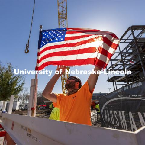 A Hausmann Construction employee unfurls a flag placed on the final steel beam during the topping out ceremony on April 9. The ceremony has roots to an ancient Scandinavian tradition that, in modern times, signals the completion of the internal structure of a building. Topping out ceremony for the new construction atop the demolished Mabel Lee Hall. April 9, 2021. Photo by Craig Chandler / University Communication.