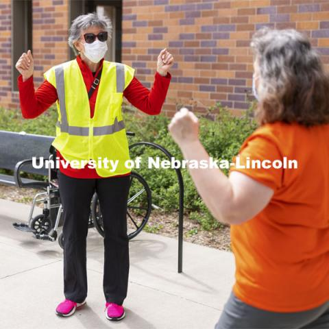 Jane Green cheers with a vaccinated person leaving the clinic Friday afternoon. Chancellor Ronnie Green and Jane Green volunteer Friday afternoon at the COVID Vaccine Clinic at Pinnacle Bank Arena. April 9, 2021. Photo by Craig Chandler / University Communication.
