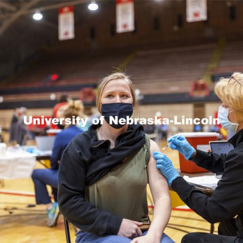 Whitney Steckel receives her first dose of vaccine during a COVID-19 vaccination clinic April 20 at the Coliseum. Vaccine clinic in the Coliseum with a free food and goodies tent outside. April 20, 2021. Photo by Craig Chandler / University Communication.