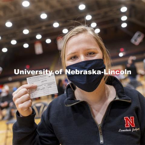 Whitney Steckel shows her vaccine card during Tuesday's clinic. Vaccine clinic in the Coliseum with a free food and goodies tent outside. April 20, 2021. Photo by Craig Chandler / University Communication.