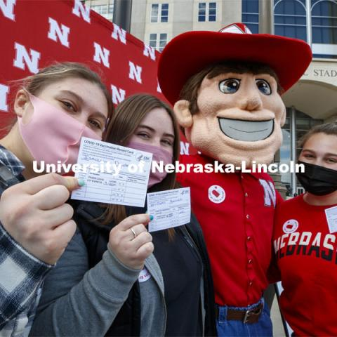 Huskers show off their vaccine cards with Herbie Husker at the after-vaccine party in the parking lot of East Stadium. Vaccine clinic in the Coliseum with a free food and goodies tent outside. April 20, 2021. Photo by Craig Chandler / University Communication.