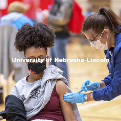Meklit Aga receives her first dose of vaccine during a COVID-19 vaccination clinic April 20 at the Coliseum. Vaccine clinic in the Coliseum with a free food and goodies tent outside. April 20, 2021. Photo by Craig Chandler / University Communication.