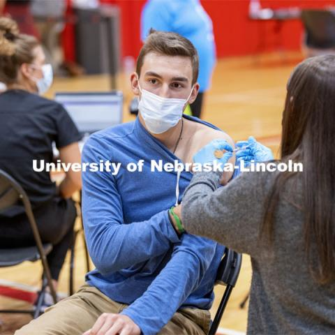 Dayton Mays receives his first dose of vaccine during a COVID-19 vaccination clinic April 20 at the Coliseum. Vaccine clinic in the Coliseum with a free food and goodies tent outside. April 20, 2021. Photo by Craig Chandler / University Communication.