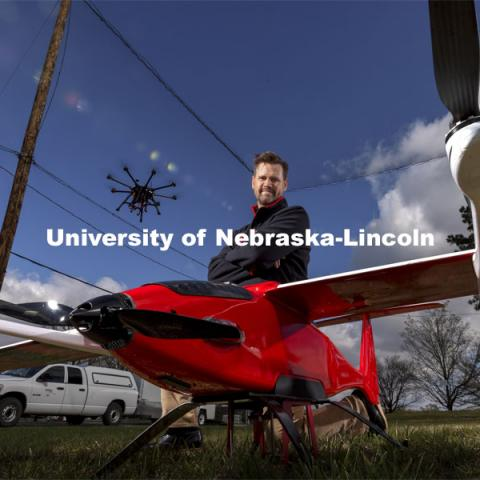 Justin Bradley, Assistant Professor in Computer Science and Engineering, is a NSF CAREER award winner. He is shown with a Savant fixed wing VTOL as a quadcopter hovers overhead. April 21, 2021. Photo by Craig Chandler / University Communication.
